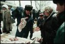Image of Street vendor weighs piece of poultry for his customer, Moscow, Russia